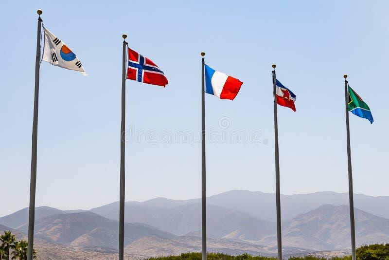 Flaggor av olika länder med berg i bakgrunden arkivbild