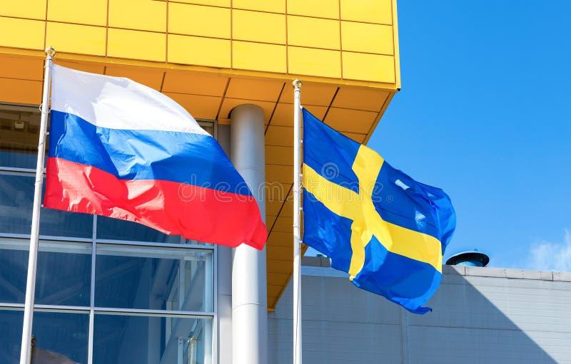 Flaggor av Sverige och Ryssland som vinkar mot det IKEA lagret royaltyfri bild