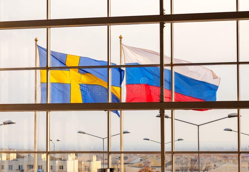 Flaggor av Sverige och Ryssland som vinkar mot fönster arkivfoto