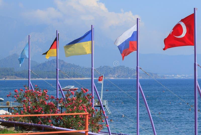 Flaggor av Turkiet, Ryssland, Ukraina, Tyskland och Kasakhstan p? stranden i Kemer fotografering för bildbyråer