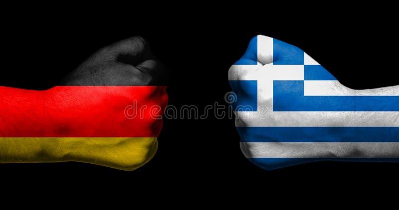 Flaggor av Tyskland och Grekland som målades på två, grep hårt om att vända mot för nävar arkivfoton