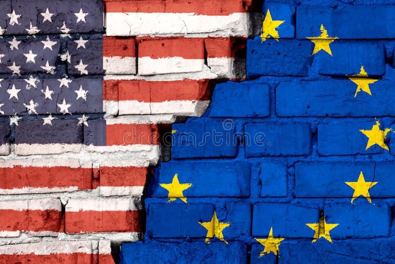 Flaggor av USA och EU för europeisk union på tegelstenväggen med den stora sprickan i mitt Symbol av problem mellan länder royaltyfri foto