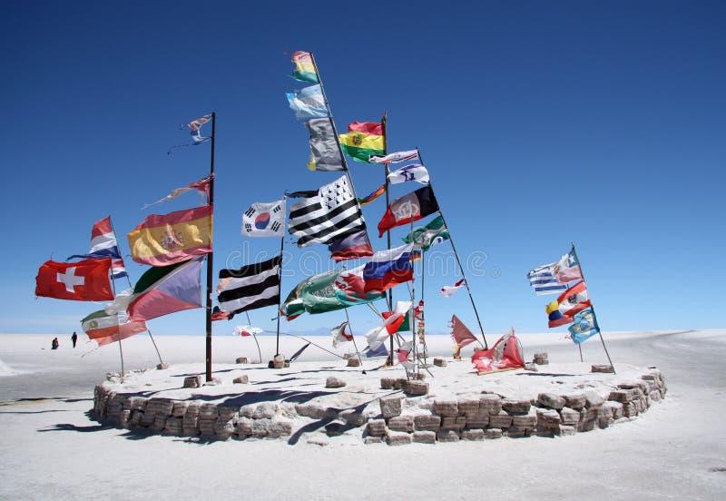 Flaggor i en salt öken av Salar de Uyuni arkivfoto