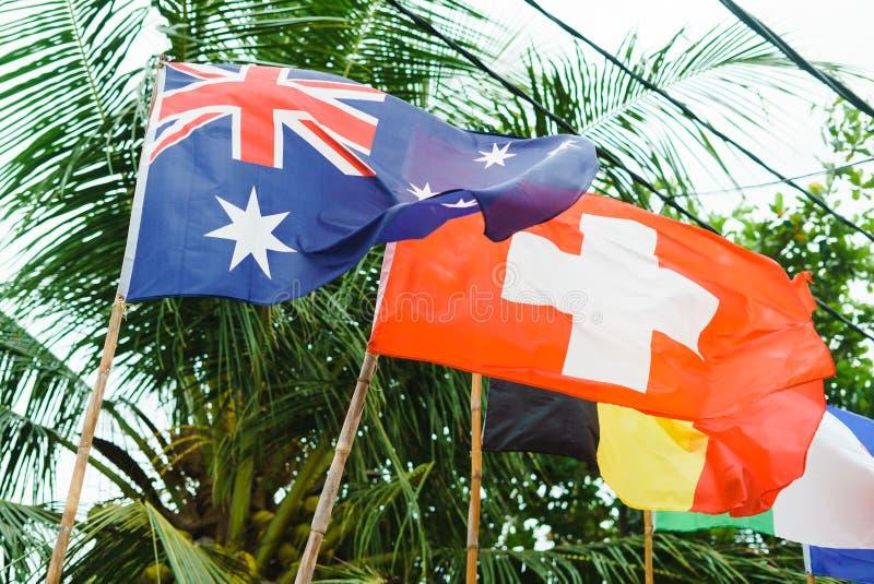Flaggor i ett varmt land mot bakgrunden av palmträd England tyskt argt rött royaltyfria bilder