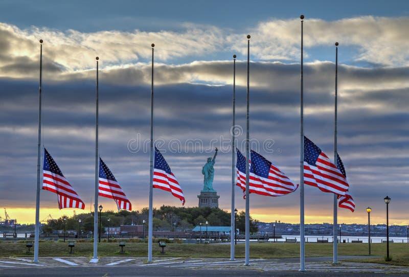 Flaggor på den halva personalen framme av statyn av frihet arkivbild