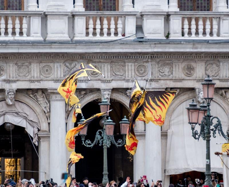 Flaggor som kastas i luften på fyrkanten för St Mark ` s under den Festa delleMaria ceremonin Venedig karneval, Italien arkivbild