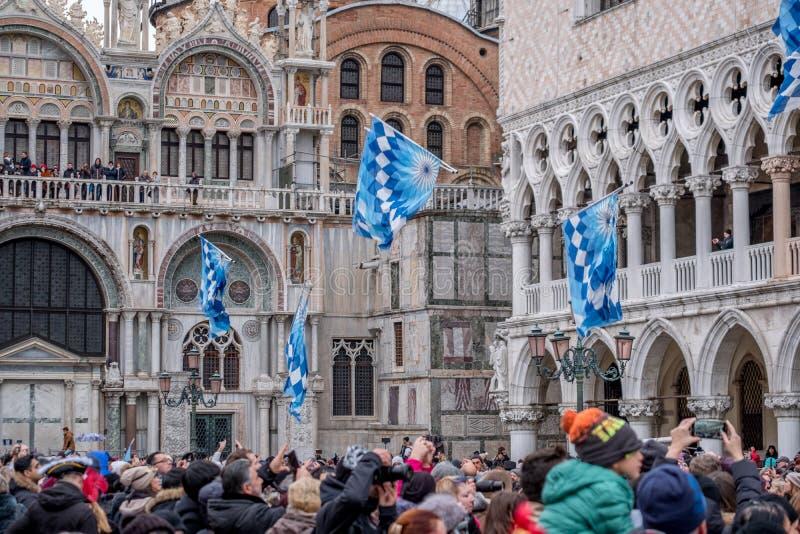 Flaggor som kastas i luften på fyrkanten för St Mark ` s under den Festa delleMaria ceremonin Venedig karneval, Italien royaltyfri bild
