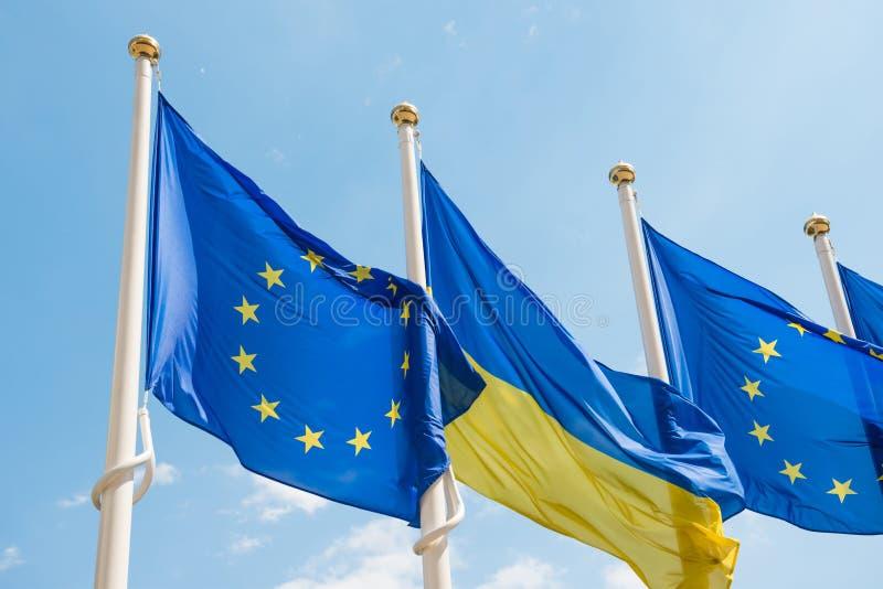 Flaggstång med flaggor för europeisk union och Ukraina på bakgrund för blå himmel royaltyfri foto