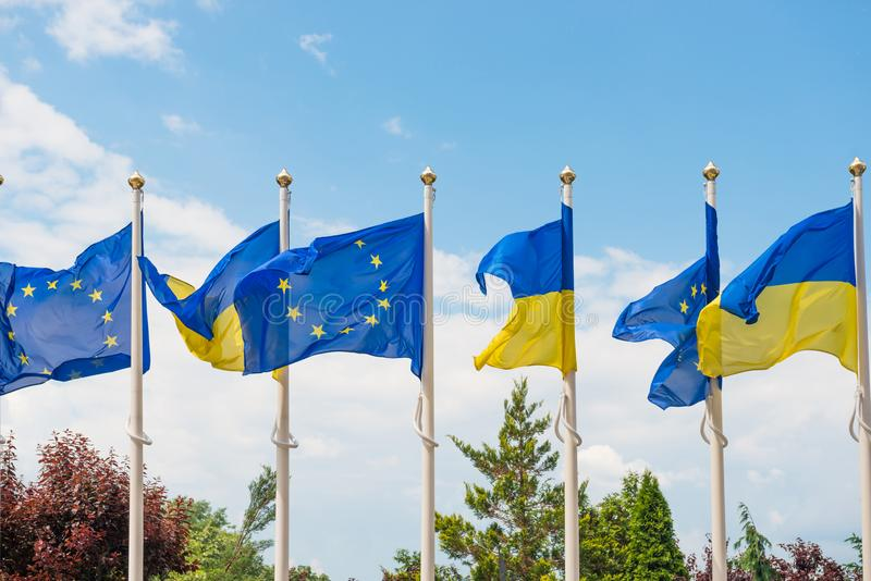 Flaggstång med flaggor för europeisk union och Ukraina på bakgrund för blå himmel royaltyfria foton
