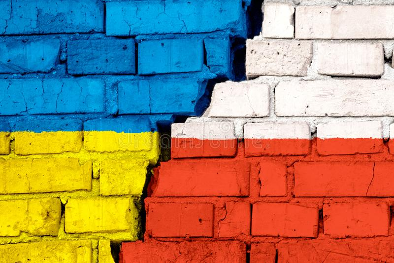 Flagi Ukraina i Polska na ścianie z cegieł z dużym pęknięciem w środku Symbol problemy mi?dzy krajami zdjęcie royalty free