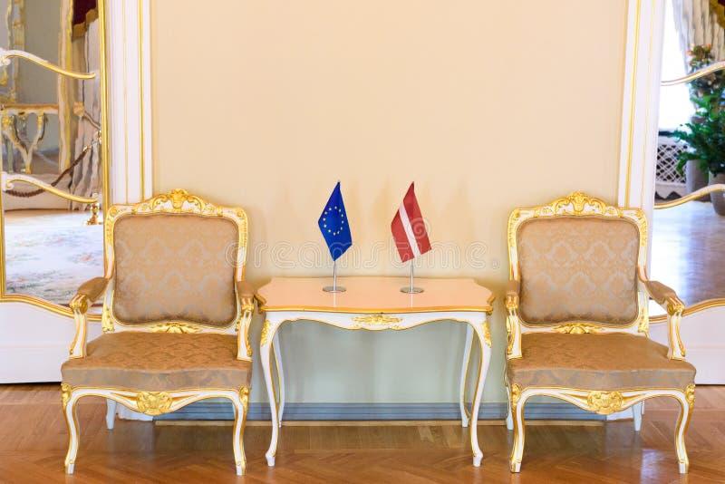 Flagi unia europejska i Latvia na stole obraz stock