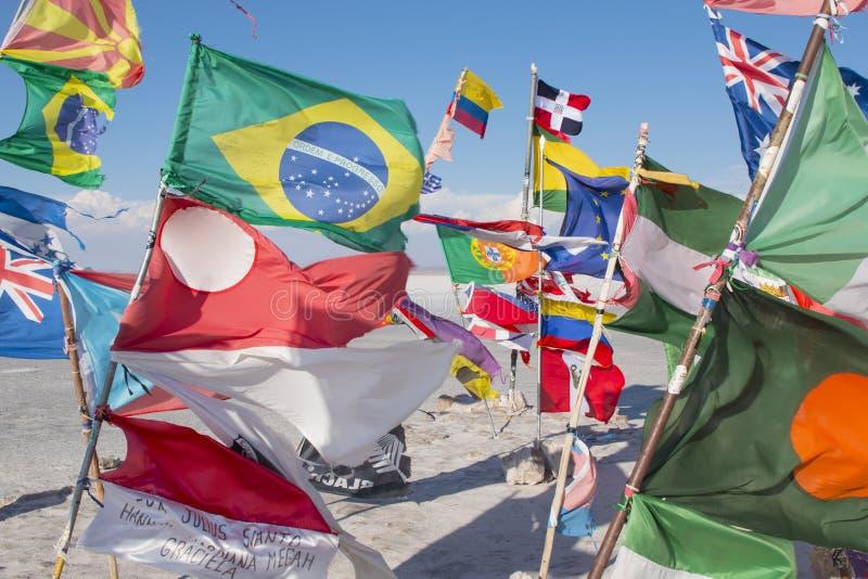 Flagi w solankowej pustyni Salar De Uyuni w Boliwia fotografia stock
