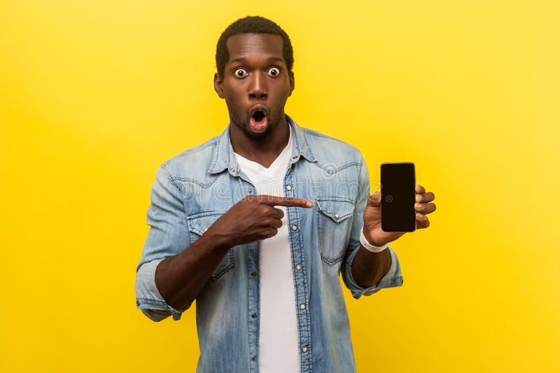 Flagman gadget. Portrait of amazed man pointing at cellphone. indoor studio shot isolated on yellow background. Flagman gadget. Portrait of amazed man in denim royalty free stock photos
