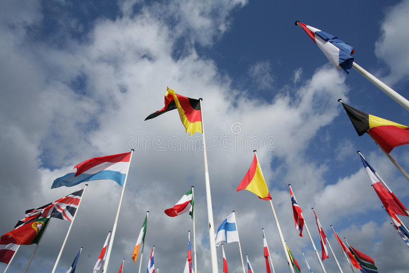 Flags. European flags in the wind and sun with gray sky stock images