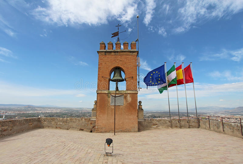 Flags atop the Alcazaba of the Alhambra in Granada, Spain. Flags and a crenellated bell tower at the highest point of the Alcazaba fortress of the Alhambra in stock images