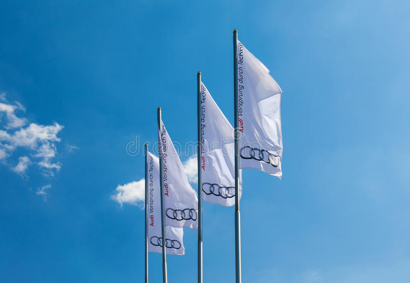 The flags of Audi over blue sky. Audi AG is a German automobile manufacturer. Audi oversees worldwide operations from its headquarters in Ingolstadt; Bavaria royalty free stock images