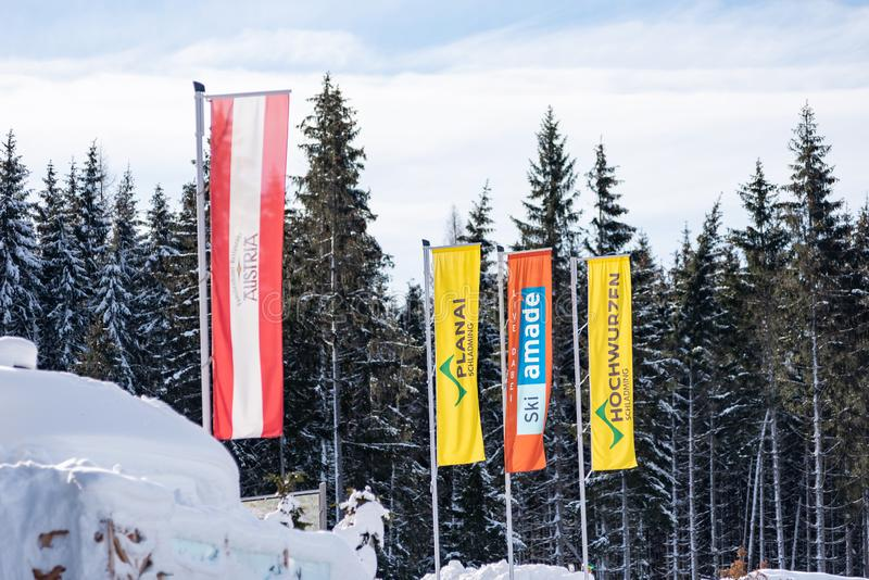 The flags of: Austria, Planai, Ski Amade, Hochwurzen at the ski region Schladming Dachstein with trees at the background.  stock images