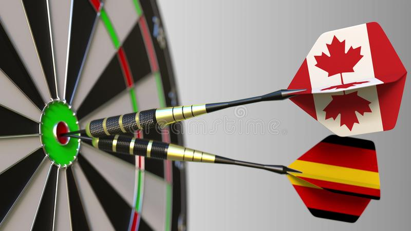 Flags of Canada and Germany on darts hitting bullseye of the target. International cooperation or competition conceptual. Flags of Canada and Germany on darts royalty free stock photo