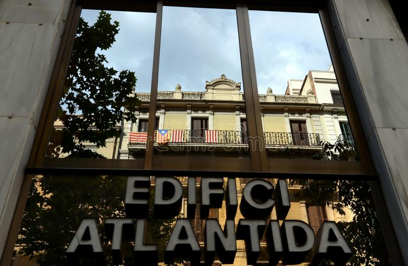 Flags of Catalonia on the balcony in the reflection of a window in Barcelona. royalty free stock photo