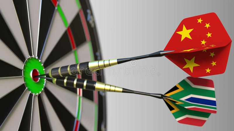 Flags of China and South Africa on darts hitting bullseye of the target. International cooperation or competition. Flags of China and South Africa on darts stock photos