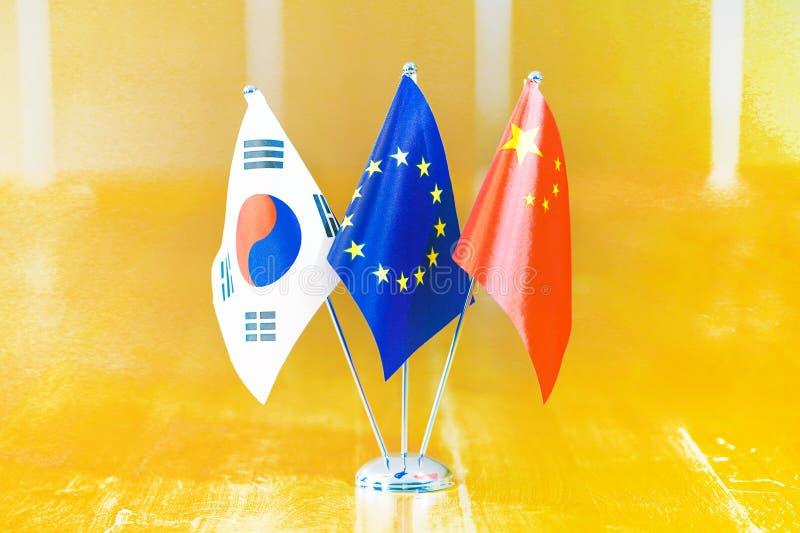 Flags of China, South Korea and European Union. Three flags on the table. Flags of South Korea, European Union and China. Flags of South Korea, European Union royalty free stock photos