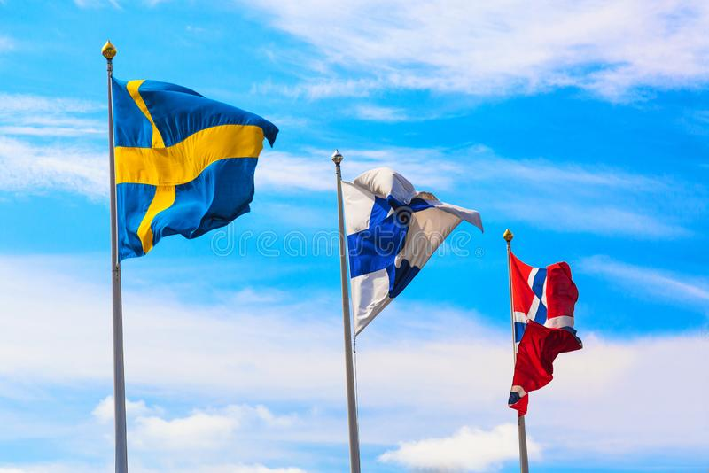 The flags of the countries of Scandinavia Sweden, Finland and Norway waving in the blue sky during beautiful summer day royalty free stock photo