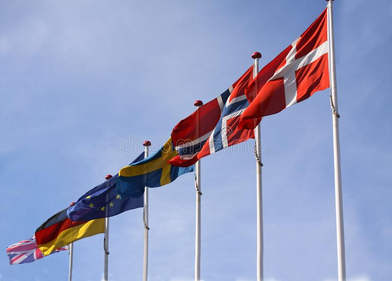 Flags from Denmark, Norway, Sweden, Germany and United Kingdom waving from flagpoles together with the EU, European Union, flag ag royalty free stock image