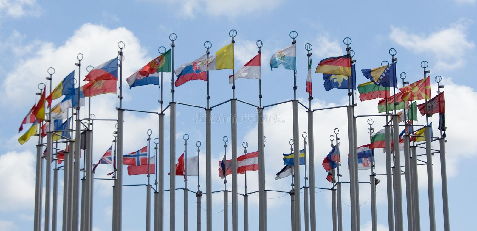 Flags of different countries. On cloudy blue sky background royalty free stock image