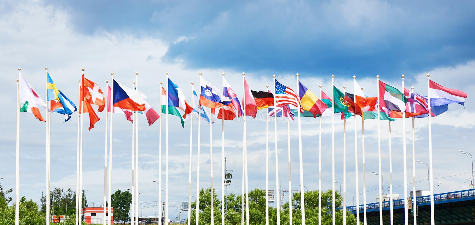Flags of different countries. On high flagpoles stock photo