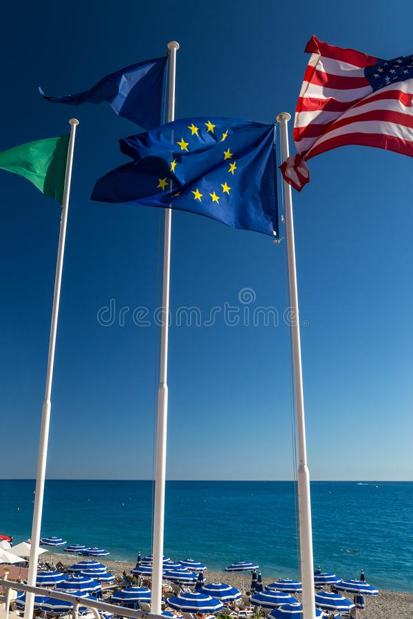 Flags of the EU and the US. European and American flags flying in the background of the sky and the sea stock photography