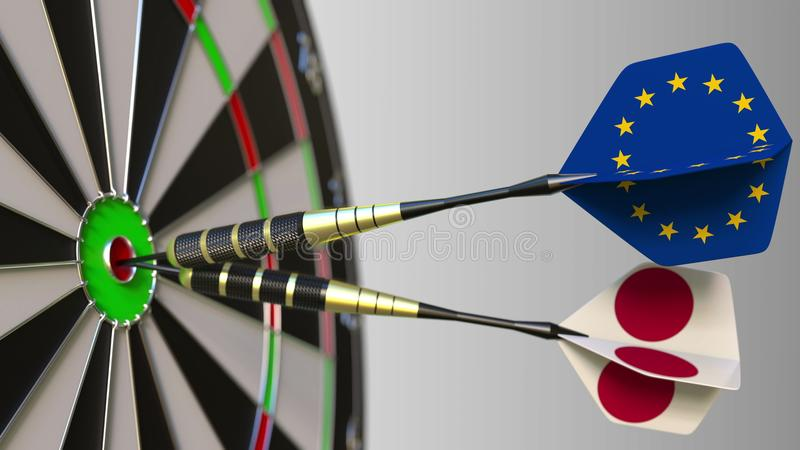 Flags of the European Union and Japan on darts hitting bullseye of the target. International cooperation or competition. Flags of the European Union and Japan on royalty free stock photography