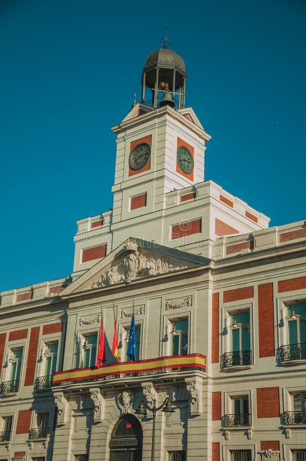 Flags on exquisite old building with bell tower and clock in Madrid. Flags on exquisite old building with plaster decoration and bell tower with clock, in a stock photo