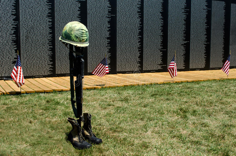 Flags and fallen soldier symbol at the wall. American flags and the symbol of the fallen soldier stand in front of the traveling vietnam war memorial wall royalty free stock photo