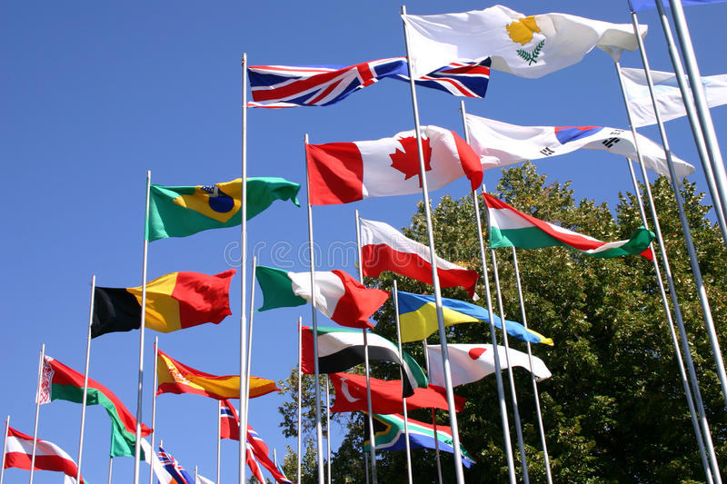 Flags on flagpoles. Develop wind stock image