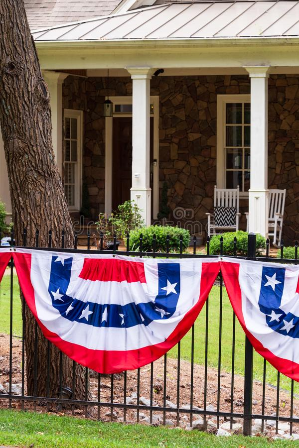 Flags flying on the fence by the front porch of the house stock photos