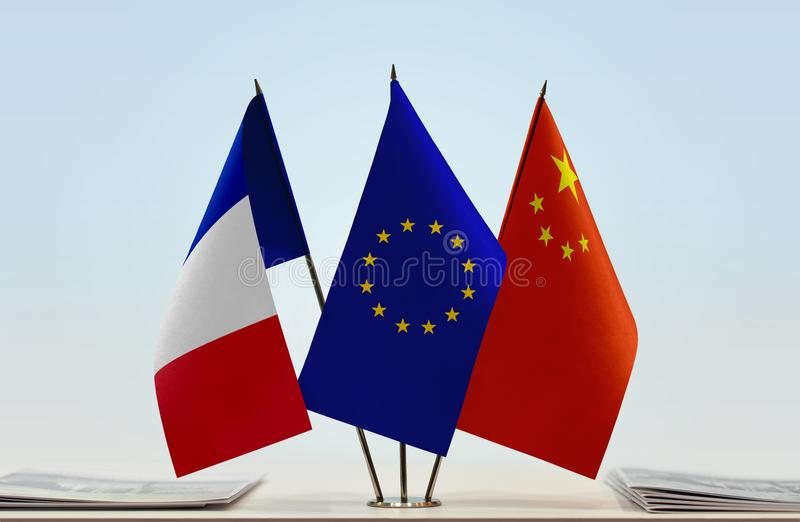 Flags of France EU and China. Desktop flags of France and China with European Union flag in the middle stock images