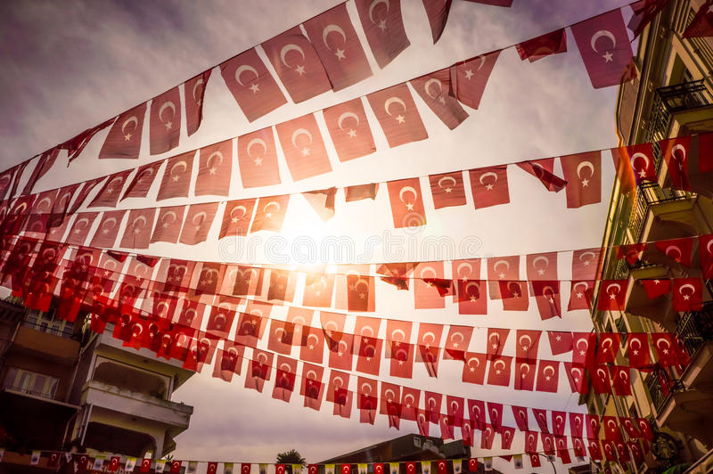 Flags. Garlands of festive turkish flags on sunny sky background. Toned image stock photo