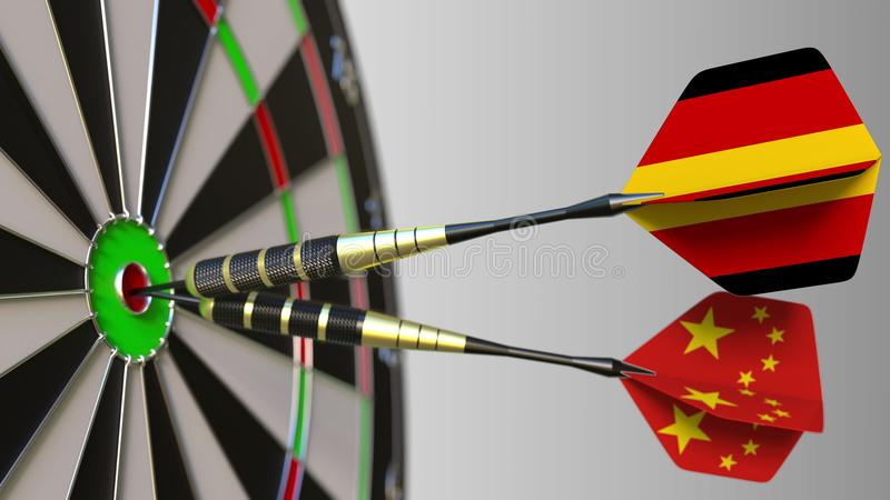 Flags of Germany and China on darts hitting bullseye of the target. International cooperation or competition conceptual. Flags of Germany and China on darts royalty free stock photo