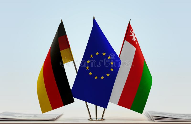 Flags of Germany EU and Oman. Desktop flags of Germany and Oman with European Union flag in the middle stock photography