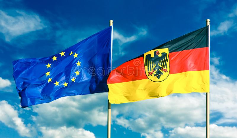 Flags of Germany Federal Republic of Germany; in German: Bundesrepublik Deutschland and European Union EU waving. In the wind on bright sunny summer day and royalty free stock photo