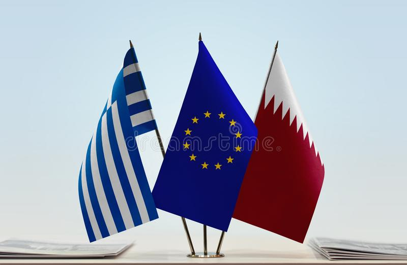 Flags of Greece EU and Qatar. Desktop flags of Greece and Qatar with European Union flag in the middle royalty free stock photo