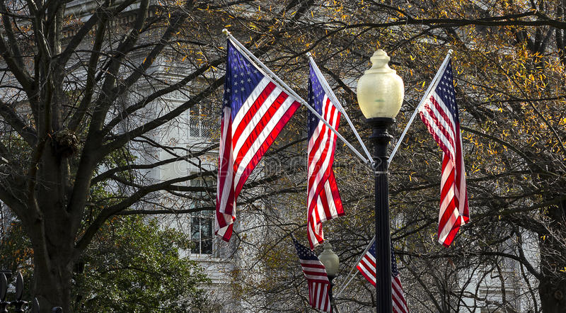 Flags hanging from streetlight. In front of the white house there is hanging flags from the streetlamps royalty free stock photography