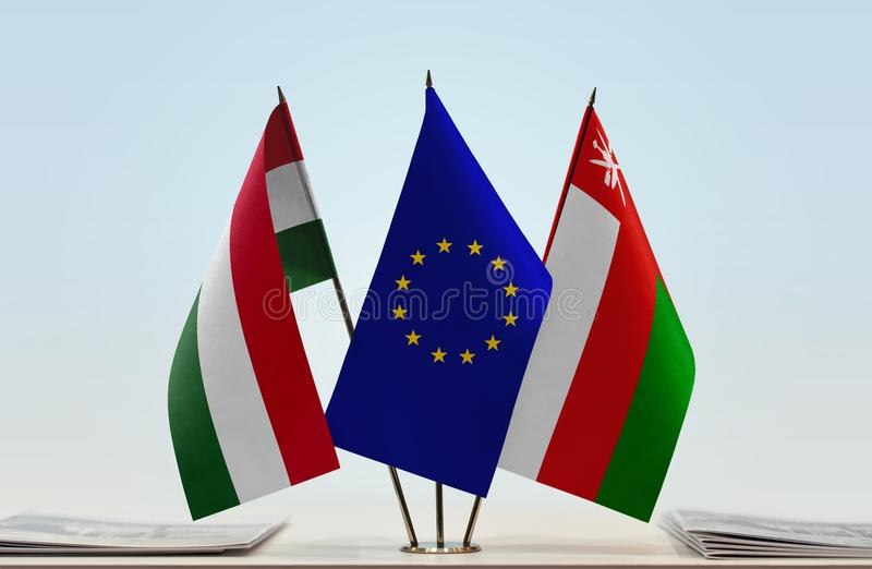 Flags of Hungary EU and Oman. Desktop flags of Hungary and Oman with European Union flag in the middle stock photography