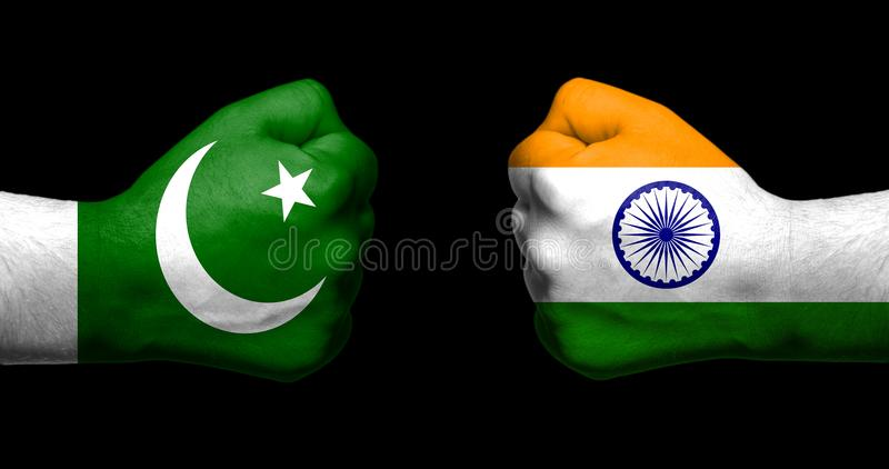Flags of India and Pakistan painted on two clenched fists facing. Each other on black background/India - Pakistan relations concept stock image