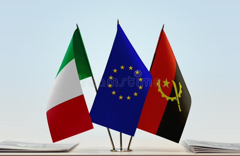 Flags of Italy EU and Angola. Desktop flags of Italy and Angola with European Union flag in the middle stock photography