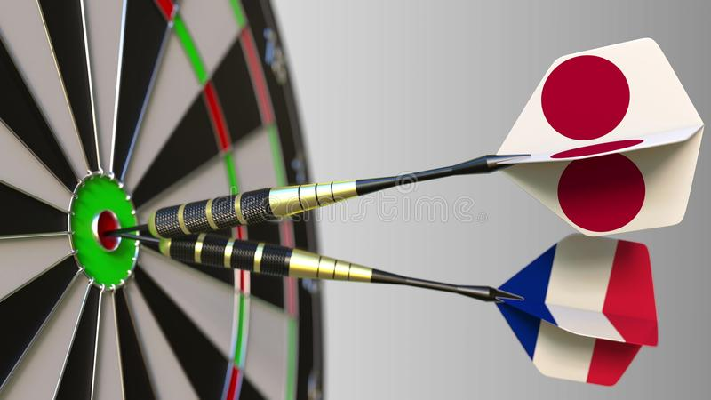 Flags of Japan and France on darts hitting bullseye of the target. International cooperation or competition conceptual. Flags of Japan and France on darts royalty free stock photo