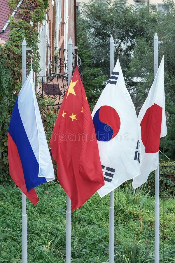 Flags of Japan, Russia, China, Republic of Korea on the flagpoles royalty free stock photos