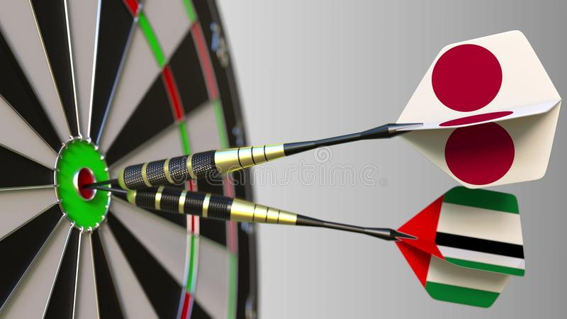 Flags of Japan and the UAE on darts hitting bullseye of the target. International cooperation or competition conceptual. Flags of Japan and the UAE on darts stock photo