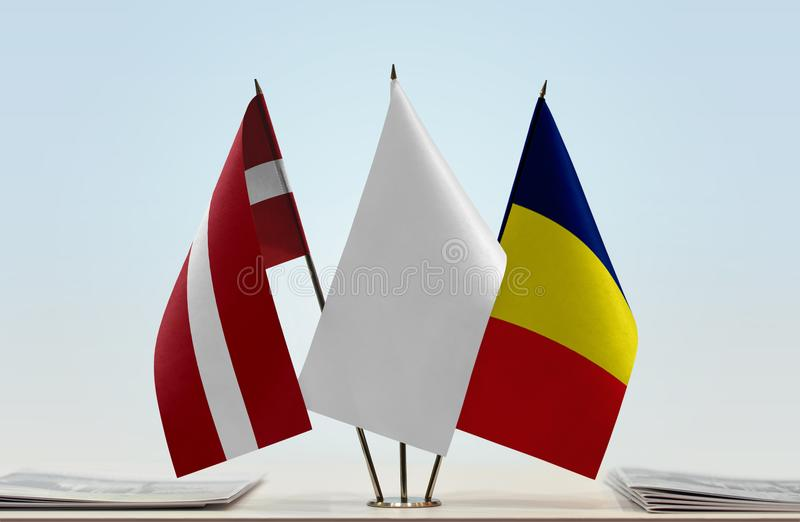 Flags of Latvia and Chad. Desktop flags of Latvia and Chad with white flag in the middle royalty free stock photo