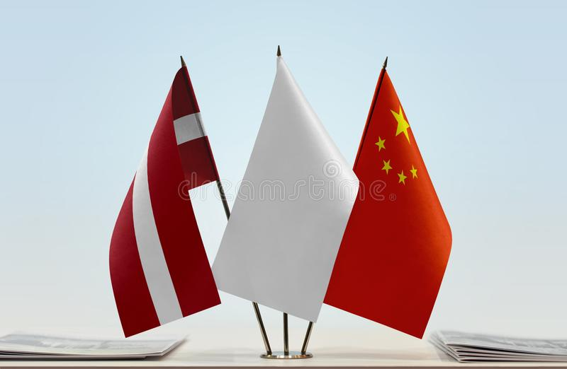 Flags of Latvia and China. Desktop flags of Latvia and China with white flag in the middle royalty free stock photo